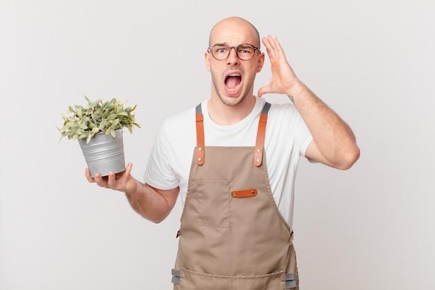 Mężczyzna ogrodnik krzyczy z rękami w górze, czuje się wściekły, sfrustrowany, zestresowany i zdenerwowany