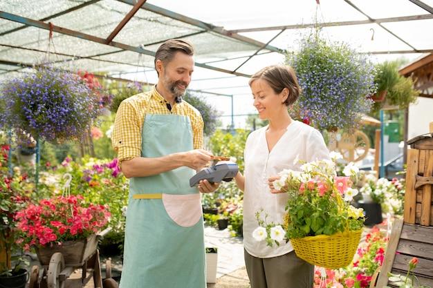 Mężczyzna ogrodnik lub sprzedawca w fartuchu sprzedający kwiaty doniczkowe ładnej kobiecie z koszykiem i korzystający z aplikacji do płatności zbliżeniowych