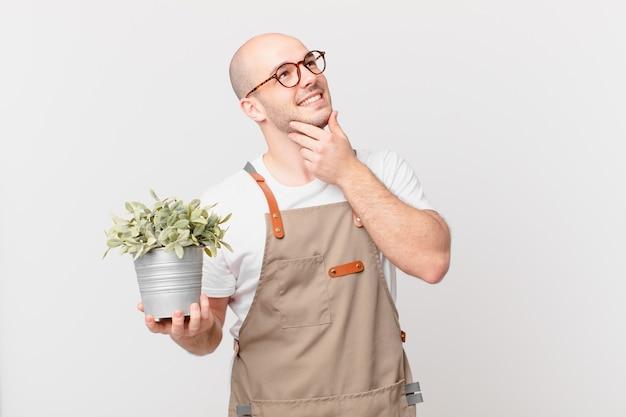 Mężczyzna ogrodnik uśmiechający się radośnie i marzący lub wątpiący, patrząc w bok