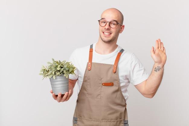 Mężczyzna ogrodnik uśmiechający się radośnie i radośnie, machający ręką, witający cię i pozdrawiający lub żegnający się