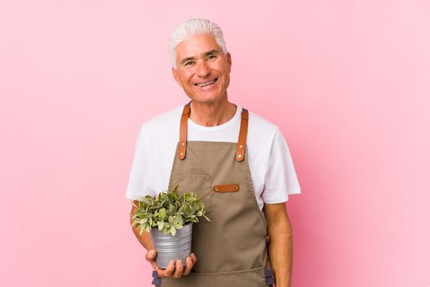 Mężczyzna ogrodnik w średnim wieku szczęśliwy, uśmiechnięty i wesoły