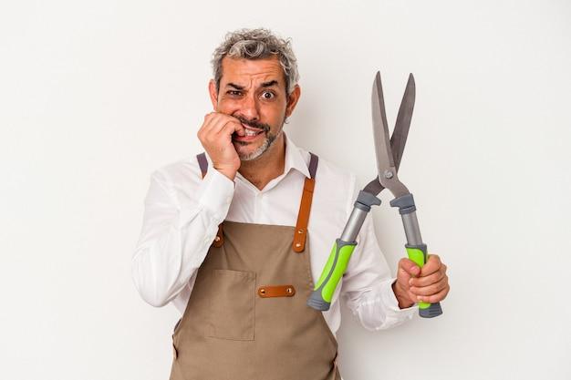 Mężczyzna ogrodnik w średnim wieku trzyma nożyczki na białym tle gryząc paznokcie, nerwowy i bardzo niespokojny.