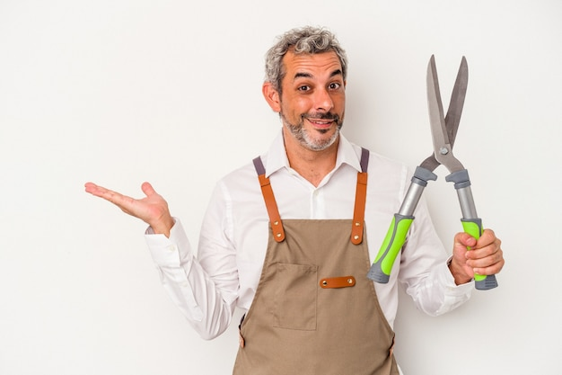 Mężczyzna ogrodnik w średnim wieku trzyma nożyczki na białym tle na białym tle pokazując miejsce na kopię na dłoni i trzymając drugą rękę na pasie.