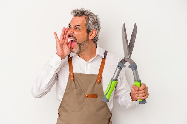 Mężczyzna ogrodnik w średnim wieku trzymając nożyczki na białym tle krzycząc i trzymając dłoń w pobliżu otwartych ust.