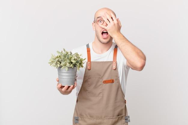 Mężczyzna ogrodnik wyglądający na zszokowanego, przestraszonego lub przerażonego, zakrywający twarz dłonią i zerkający między palcami