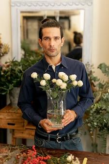 Mężczyzna ogrodnik z długimi włosami gospodarstwa kwiaty