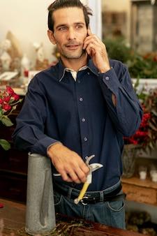 Mężczyzna ogrodnik z długimi włosami rozmawia przez telefon