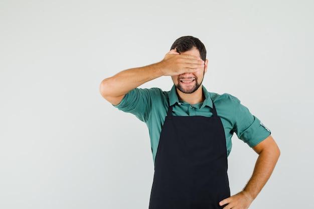 Mężczyzna ogrodnik zakrywający oczy dłonią w koszulce, fartuchu i wyglądający na podekscytowanego. przedni widok.