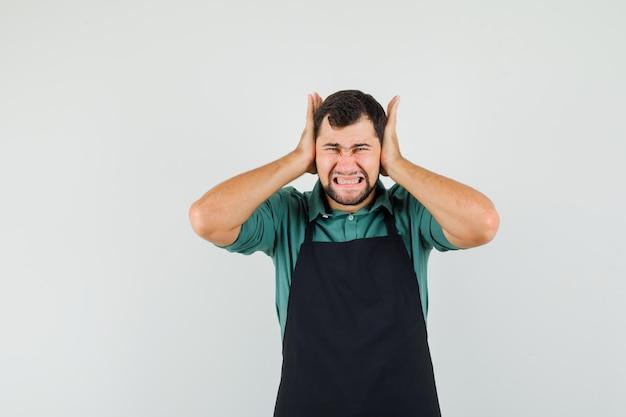 Mężczyzna ogrodnik zakrywający uszy rękami w koszulce, fartuchu i wyglądający na zirytowanego. przedni widok.