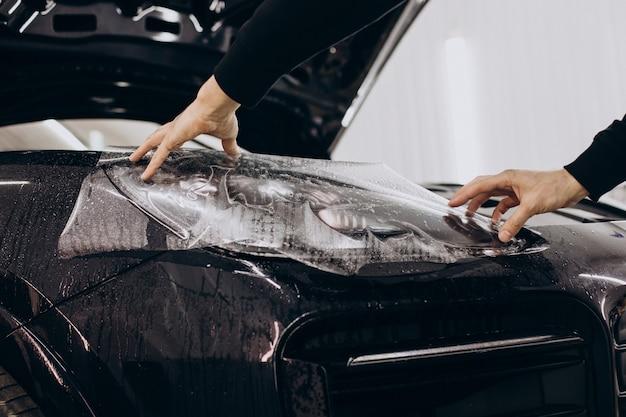 Mężczyzna oklejający samochód folią ptotective