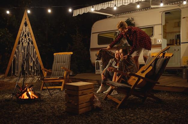 Mężczyzna okrywa dziewczyny w kratę przy ognisku w nocy, piknik na kempingu w lesie. młodzież ma letnią przygodę na rv, samochód kempingowy wypoczynek dla par, podróżowanie z przyczepą
