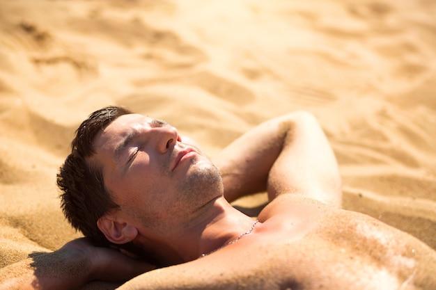Mężczyzna opala się na gorącym żółtym piasku. wakacje na plaży, kurort nad brzegiem morza. ochrona przeciwsłoneczna, promienie uv, filtr przeciwsłoneczny, spf. zdrowie skóry