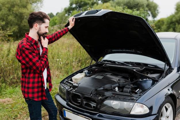 Mężczyzna oparty na otwartej masce samochodu
