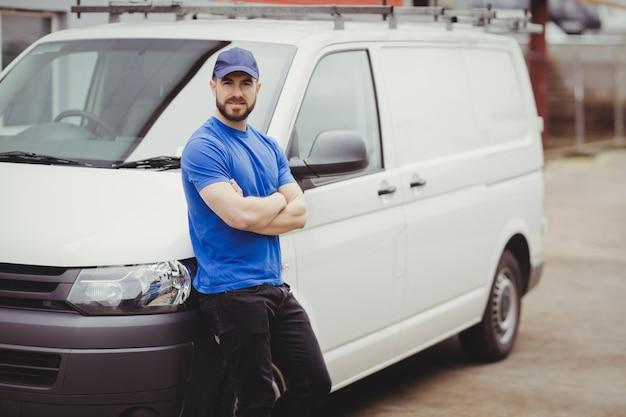 Mężczyzna oparty o swoją furgonetkę ze skrzyżowanymi rękami
