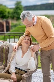 Mężczyzna opiekujący się żoną siedzącą w fotelu