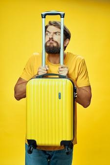 Mężczyzna opiera łokcie na żółtej walizce z rękami turystyka podróżnicza