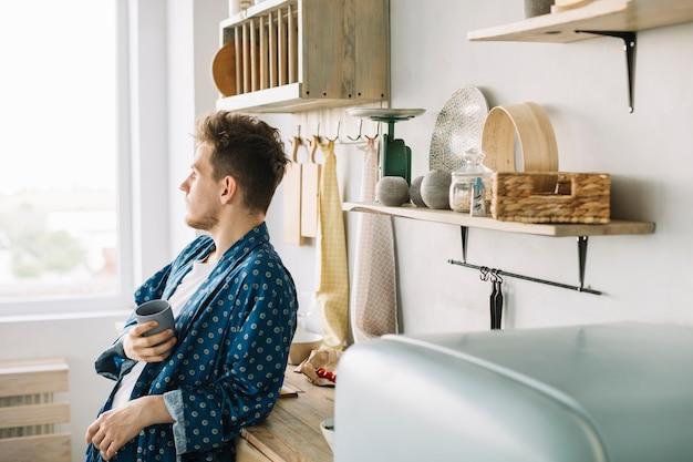 Mężczyzna opiera na kuchennym kontuarze trzyma filiżankę kawy
