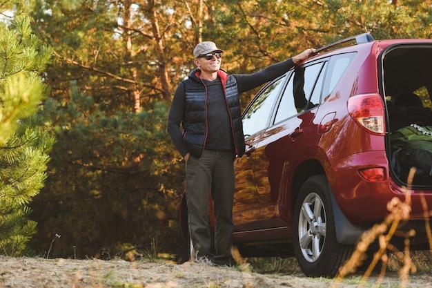 Mężczyzna opiera się na dachu samochodu na tle przyrody