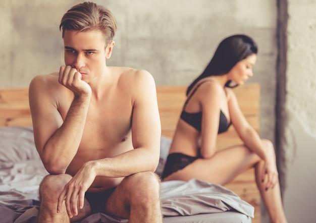 Mężczyzna opiera się na dłoni, siedząc ze smutkiem na łóżku