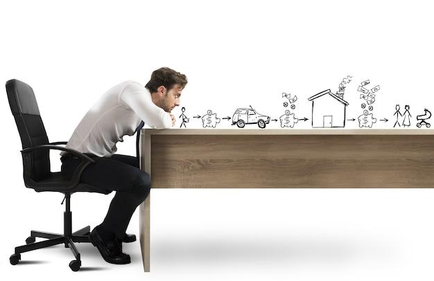 Mężczyzna opierając się na biurku z zamyślonym wyrazem twarzy