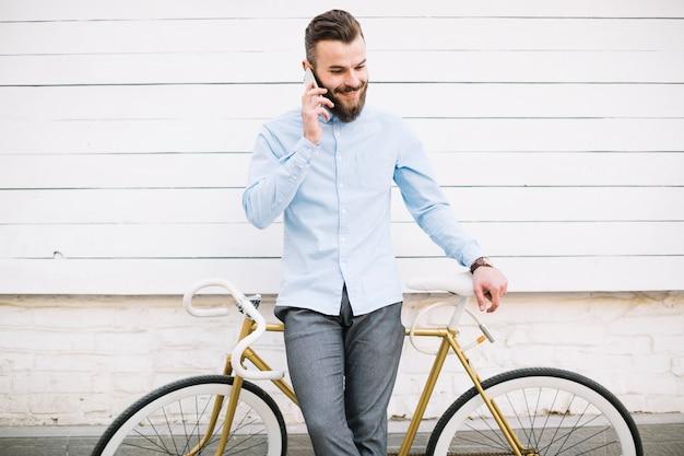 Mężczyzna opowiada na telefonie blisko biel ściany