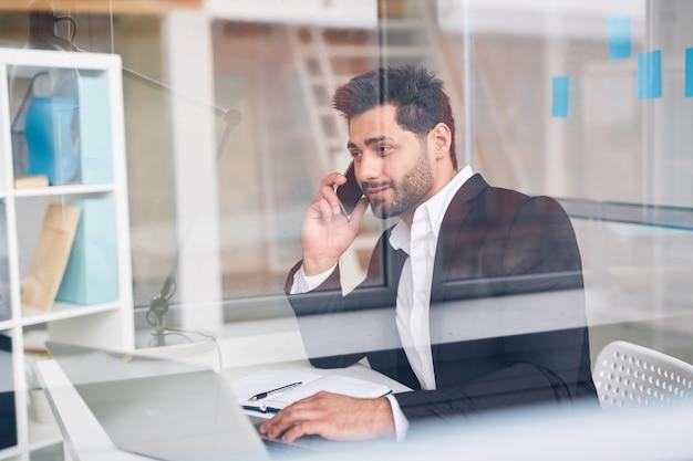 Mężczyzna opowiada telefonem przy biurem