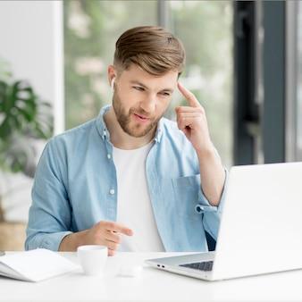 Mężczyzna opowiada wideo na laptopie