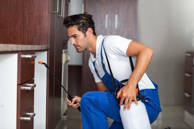Mężczyzna opryskiwania pestycydem w kuchni