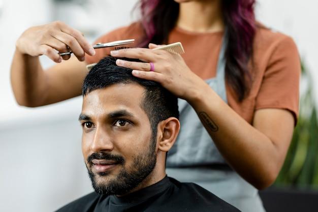 Mężczyzna ostrzyżony u fryzjera w zakładzie fryzjerskim