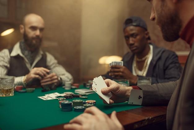 Mężczyzna oszukuje w pokera przy stole do gier, kasyno. uzależnienie, ryzyko, dom hazardowy