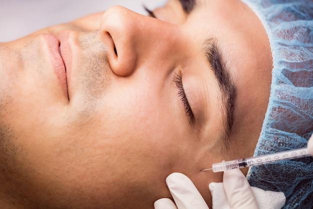 Mężczyzna otrzymujący zastrzyk botoksu na jego twarzy