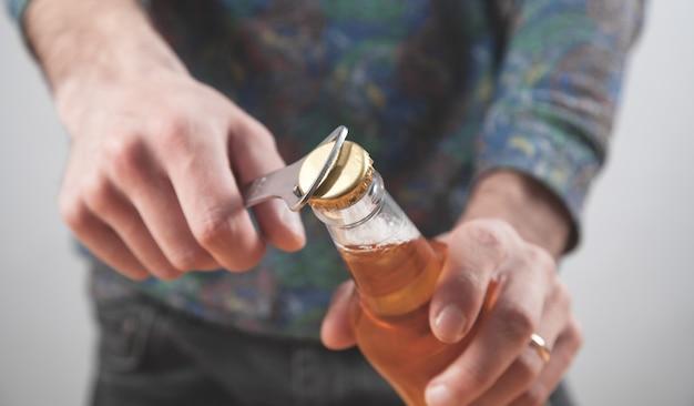 Mężczyzna otwiera butelkę piwa