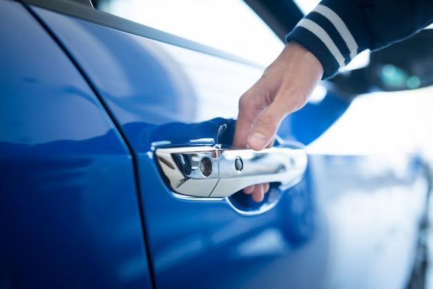 Mężczyzna otwiera drzwi do nowego samochodu, inspekcja samochodu w salonie