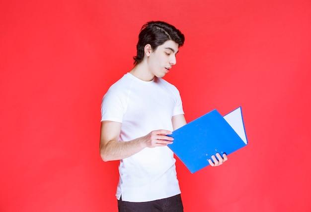 Mężczyzna otwiera i czyta niebieski folder.