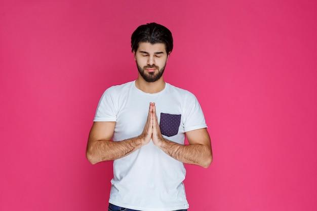 Mężczyzna otwiera i łączy ręce, aby się o coś modlić.