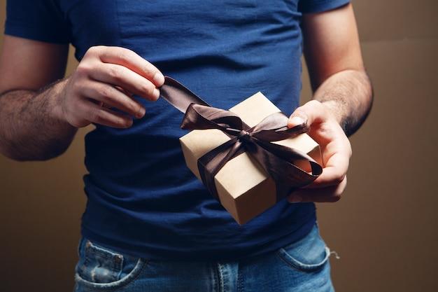 Mężczyzna otwiera prezent wstążkę na brązowym tle