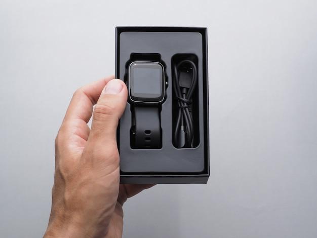 Mężczyzna otwiera pudełko nowego czarnego inteligentnego zegarka