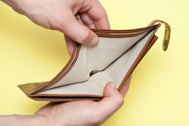Mężczyzna otwiera pustą torebkę bez pieniędzy. ścieśniać.