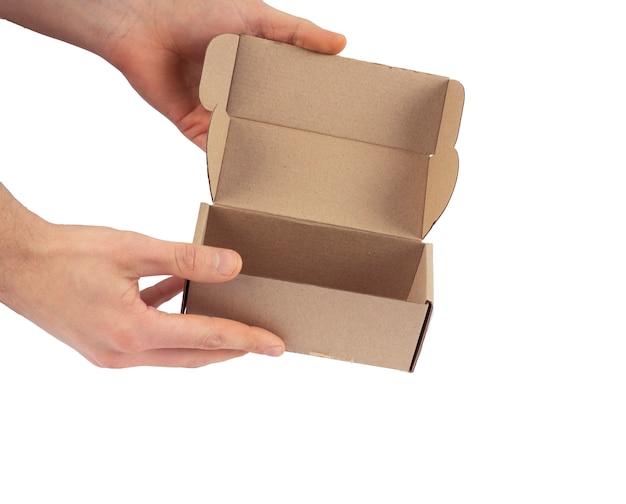 Mężczyzna otwiera pustego karton na białym tle.