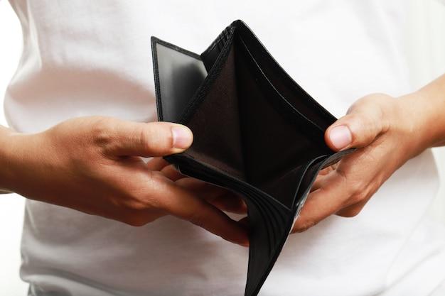 Mężczyzna otwiera pusty skórzany portfel bez pieniędzy w pustej kieszeni. bardzo ubogi.
