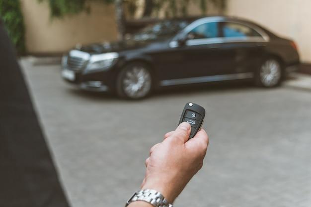 Mężczyzna otwiera samochód za pomocą pęku kluczy, w tle jest czarny samochód.