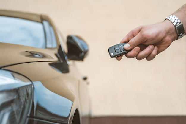 Mężczyzna otwiera samochód za pomocą pęku kluczy.