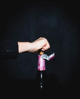 Mężczyzna otwiera świąteczną butelkę szampan