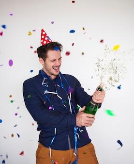 Mężczyzna otwierając butelkę szampana