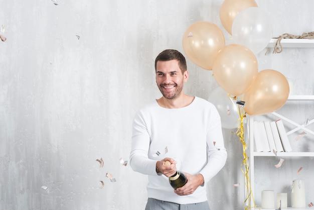 Mężczyzna otwierający butelkę szampana