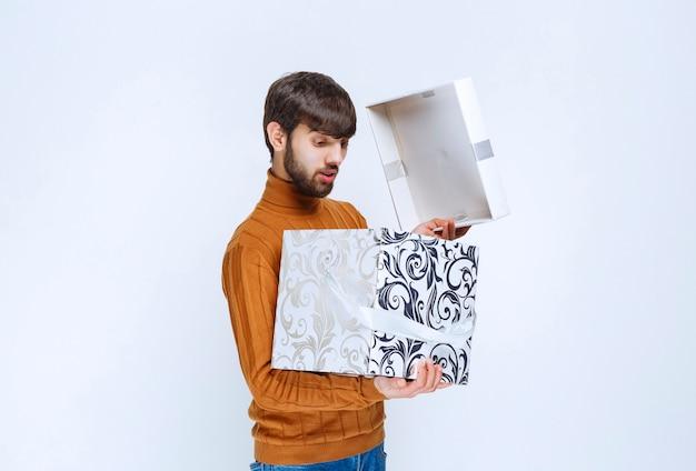 Mężczyzna otwierający i sprawdzający wnętrze białego pudełka z niebieskimi wzorami.