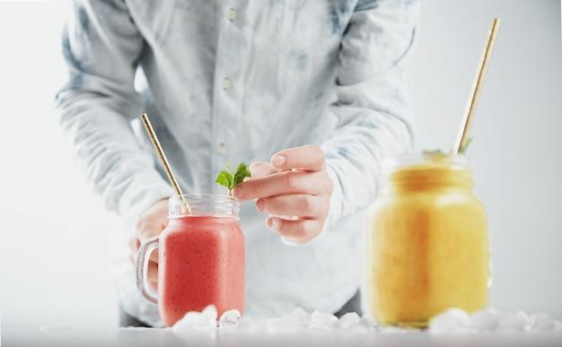 Mężczyzna ozdabia smoothie w rustykalnym słoiku listkami mięty. dwa słoiki ze zdrowymi, różnymi zimnymi koktajlami owocowymi w środku: mango