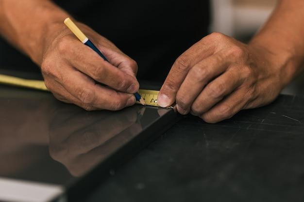 Mężczyzna oznaczający powierzchnię miernikiem w warsztacie