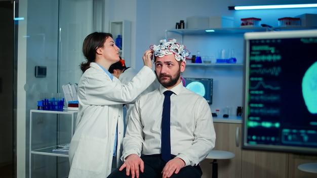 Mężczyzna pacjent odwiedzający profesjonalnego badacza medycznego w neurologii testujący funkcje mózgu za pomocą zestawu słuchawkowego eegeg