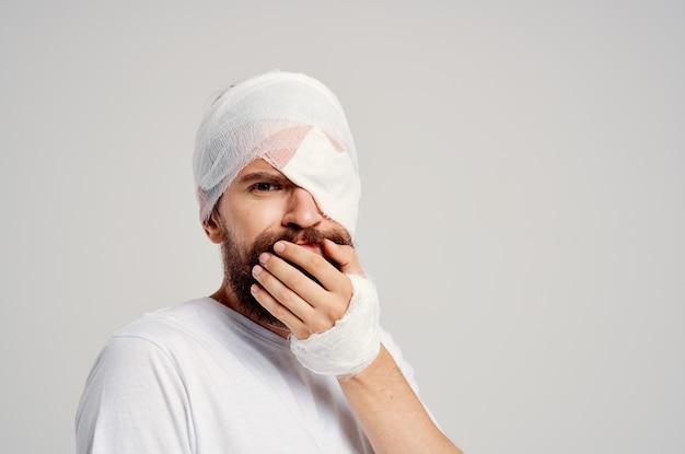 Mężczyzna pacjent z obandażowaną głową i jasnym tłem hospitalizacji oczu. zdjęcie wysokiej jakości